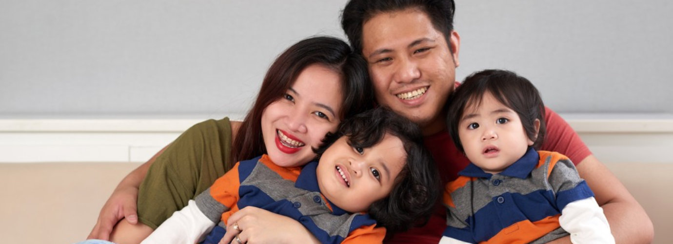 Happy Filipino man hugging his wife and two children